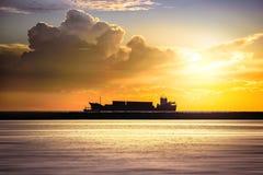 Грузовой корабль в океане на небе захода солнца Стоковая Фотография