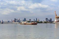 Грузовой корабль голевой передачи буксира пропуская через много городков и склад Стоковые Фото