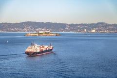 Грузовой корабль контейнера входя в San Francisco Bay и Алькатрас - Сан-Франциско, Калифорнию, США Стоковые Фотографии RF