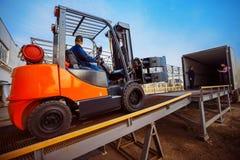 Грузоподъемник кладет груз от склада для того чтобы перевезти на грузовиках стоковые изображения