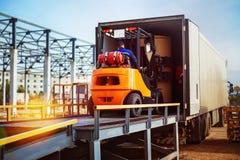 Грузоподъемник кладет груз от склада для того чтобы перевезти на грузовиках стоковые фотографии rf