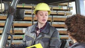 Грузоподъемник молодого женского fatory работника работая на хранении говоря к ее коллеге сток-видео