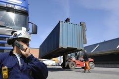Грузоподъемник поднимая груз и контейнеры для перевозок Стоковые Фотографии RF