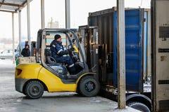 Грузоподъемник кладет груз от склада для того чтобы перевезти на грузовиках outdoors стоковая фотография rf