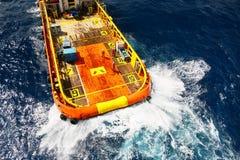 Груз переноса шлюпки поставки к нефтяной промышленности нефти и газ и moving груз от шлюпки к платформе, груз переноса шлюпки жда Стоковые Фото