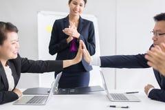 Группа в составе азиатские бизнесмены хлопать рук после встречи в комнате, представлении успеха команды и семинаре тренировать на стоковые изображения rf