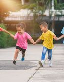 Группа в составе азиатские дети держа руки и бежать или идя tog стоковое фото