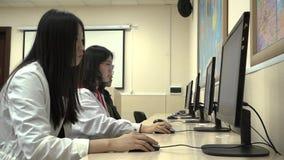 Группа в составе азиатские студенты использует компьютеры во время тренировки пока в классе видеоматериал