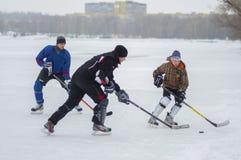 Группа в составе активная игра людей hokey на замороженном реке Dnipro в Украине стоковая фотография
