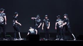 Группа в составе активные подростки и девушки в черных одеждах и крышках танцуют на этапе сток-видео