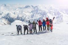 Группа в составе альпинисты счастлива и развевающ их руки в горах стоковое фото rf