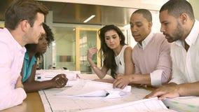 Группа в составе архитекторы обсуждая планы в современном офисе видеоматериал