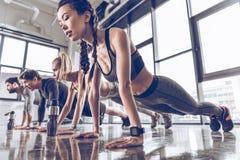 Группа в составе атлетическое молодые люди в делать sportswear нажимает поднимает или планка на спортзале Стоковая Фотография