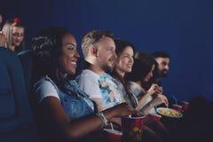 Группа в составе африканец и кавказцы смотря кино в кино стоковое фото rf
