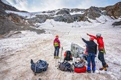 Группа в составе альпинисты обсуждает трассу перевала Стоковое фото RF