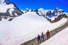 Группа в составе альпинисты смотря снег-покрытые горы и ледник Стоковые Изображения RF