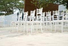 Группа в составе белые стулья на подготовке свадьбы на пляже, конусы chiavari лепестков роз - лицевой стороны, взгляда низкого уг Стоковые Изображения