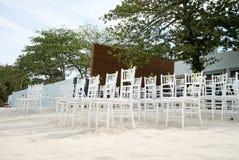 Группа в составе белые стулья на подготовке свадьбы на пляже, конусы chiavari лепестков роз - лицевой стороны, взгляда низкого уг Стоковое Изображение RF