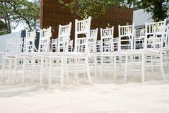 Группа в составе белые стулья на подготовке свадьбы на пляже, конусы chiavari лепестков роз - лицевой стороны, взгляда низкого уг Стоковые Изображения RF