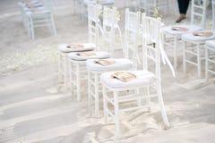 Группа в составе белые стулья на подготовке свадьбы на пляже, конусы chiavari лепестков роз - взгляда лицевой стороны Стоковые Фотографии RF