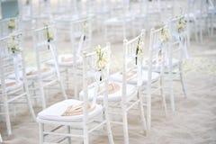 Группа в составе белые стулья на подготовке свадьбы на пляже, конусы chiavari лепестков роз - заднего взгляда со стороны Стоковое Изображение RF