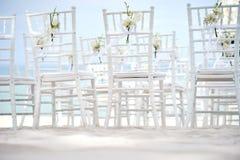 Группа в составе белые стулья на подготовке свадьбы на пляже, конусы chiavari лепестков роз - задних, взгляда низкого угла Стоковое Фото