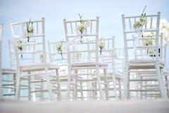 Группа в составе белые стулья на подготовке свадьбы на пляже, конусы chiavari лепестков роз - задних, взгляда низкого угла Стоковые Фото