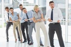 Группа в составе бизнесмены вытягивая веревочки в офисе Стоковое Изображение