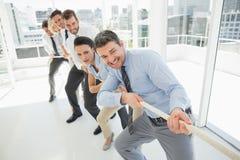 Группа в составе бизнесмены вытягивая веревочки в офисе Стоковые Фотографии RF