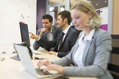 Группа в составе бизнесмены в современном офисе, работая на компьютере Стоковые Изображения RF