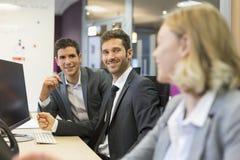 Группа в составе бизнесмены в современном офисе, работая на компьютере Стоковая Фотография
