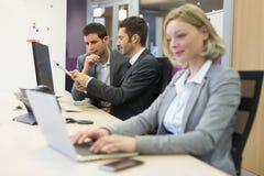 Группа в составе бизнесмены в современном офисе, работая на компьютере Стоковое Фото