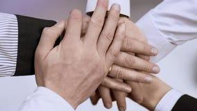 Группа в составе бизнесмены держа руки совместно, символ сыгранности и поддержку Стоковые Фото