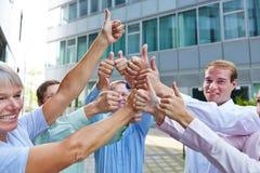 Группа в составе бизнесмены держа большие пальцы руки вверх Стоковое Изображение