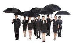 Группа в составе бизнесмены держа зонтик Стоковые Изображения RF