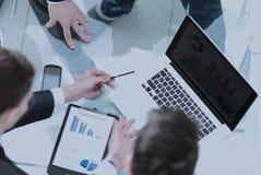 Группа в составе бизнесмены занятые обсуждающ финансовое дело во время Стоковое Изображение RF