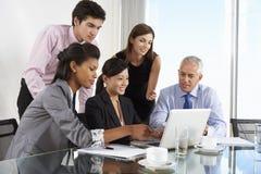 Группа в составе бизнесмены имея встречу вокруг компьтер-книжки на стекле t Стоковая Фотография RF