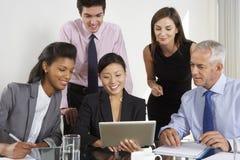 Группа в составе бизнесмены имея встречу вокруг планшета a Стоковая Фотография RF