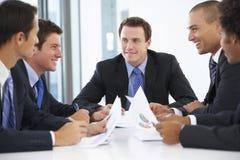 Группа в составе бизнесмены имея встречу в офисе Стоковое Изображение