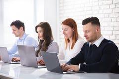 Группа в составе бизнесмены используя компьтер-книжку Стоковое Изображение RF