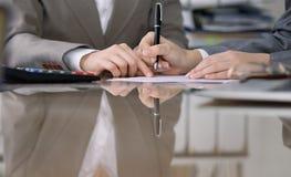 Группа в составе бизнесмены и юристы обсуждая контракт пока сидящ на таблице Вождь женщины принимает ручку для Стоковая Фотография
