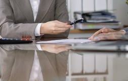 Группа в составе бизнесмены и юристы обсуждая контракт пока сидящ на таблице Вождь женщины принимает ручку для Стоковое фото RF