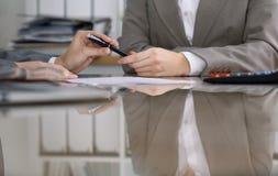 Группа в составе бизнесмены и юристы обсуждая контракт пока сидящ на таблице Вождь женщины принимает ручку для Стоковые Изображения