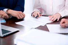 Группа в составе бизнесмены и юристы обсуждая бумаги контракта стоковое изображение rf
