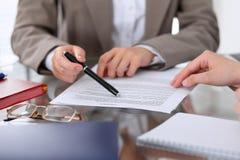 Группа в составе бизнесмены и юристы обсуждая контракт завертывает сидеть в бумагу на таблице, конец вверх Стоковые Фотографии RF
