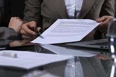 Группа в составе бизнесмены и юристы обсуждая контракт сидя на таблице Вождь женщины принимает ручку для подписания Стоковое фото RF