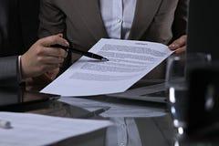 Группа в составе бизнесмены и юристы обсуждая контракт сидя на таблице Вождь женщины принимает ручку для подписания Стоковые Изображения RF