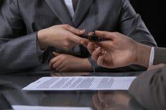 Группа в составе бизнесмены и юристы обсуждая контракт сидя на таблице Вождь женщины принимает ручку для подписания Стоковая Фотография RF