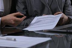 Группа в составе бизнесмены и юристы обсуждая контракт сидя на таблице Вождь женщины принимает ручку для подписания Стоковые Изображения