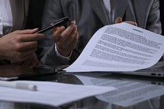 Группа в составе бизнесмены и юристы обсуждая контракт сидя на таблице Вождь женщины принимает ручку для подписания Стоковые Фотографии RF